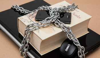 Phone, book and laptop locked under chains as a visual representation of cyber security
